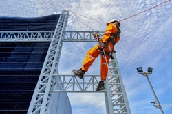 worker on high wear dresses and safety man with harness concept on steel structures success from work in site construction on blue sky background