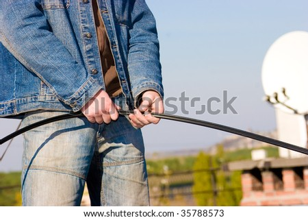 Worker on roof holding optical cable