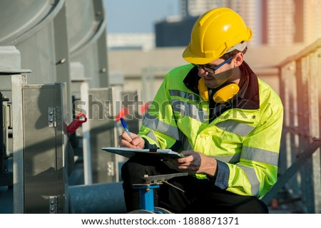 worker open valve of cooling tower on blue sky background. worker opening butterfly valve on top of cooling Tower. engineer check valve on cooling tower.