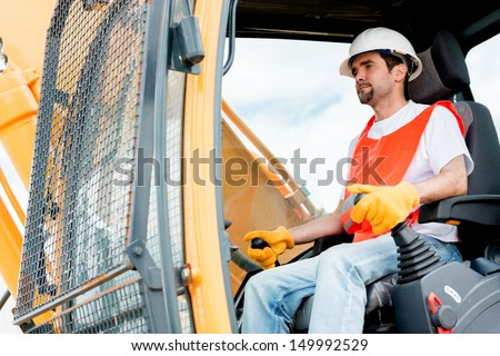 Worker operating a crane at a construction site