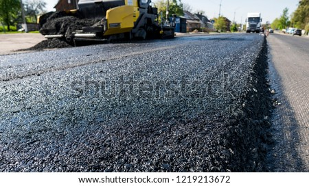 Worker operating asphalt paver machine during road construction and repairing works. A paver finisher, asphalt finisher or paving machine placing a layer of asphalt. Repaving #1219213672