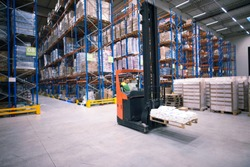 Worker operating forklift machine and relocating goods in large warehouse center.