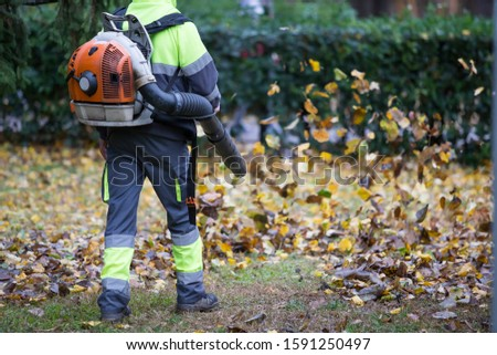 Worker operating heavy duty leaf blower in city park. Dark blue and fluor green dress.Removing fallen leaves in autumn. Leaves swirling up. Stock photo ©