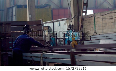 Worker or employee or mechanical technician with a crane lifts a stack of new long steel metal profiles in the warehouse. Concept for industrial worker, manual work and manufacturing.