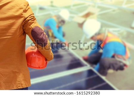 Worker or engineer holding in hands helmet for workers security on Solarcells panels on roof background. Installing solar photovoltaic panel system. Alternative energy ecological concept.