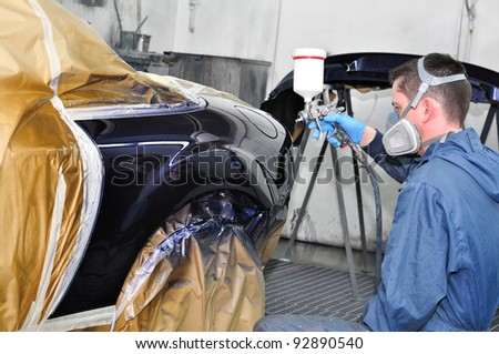 Worker painting a car