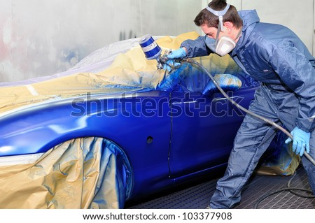 Worker painting a car in a paint booth