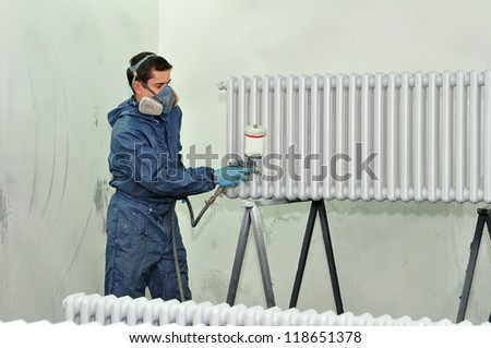 Worker painting a radiator in white.