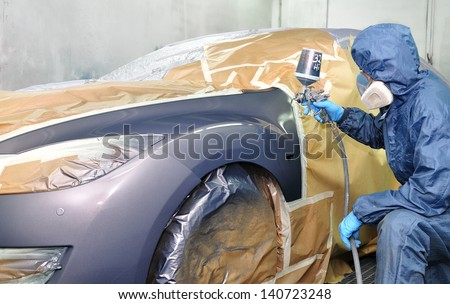 Worker painting car in a paint booth.