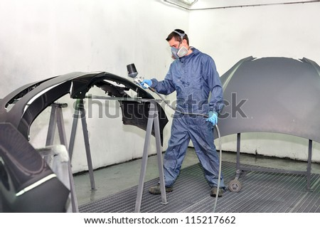 Worker painting car parts in a paint booth.