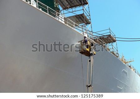 Worker painting ship hull using airbrush.