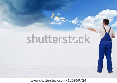 Worker painting the wall from stormy sky to fluffy clouds - with copy space
