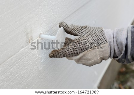Worker placing expansion anchor to styrofoam sheet insulation of the wall