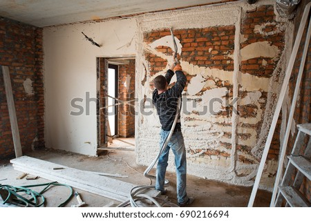 worker Plastering Walls with a plastering pump Machine on the construction of a private house