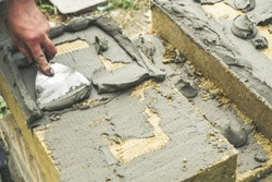 Worker plying adhesive on rock wool insulation panels