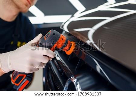 Worker polishes radiator grille, car detailing