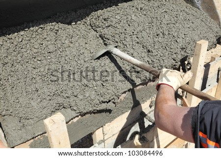 Worker pouring concrete to formwork at construction site