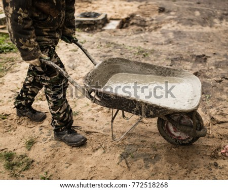 worker pours concrete mortar on a construction site #772518268