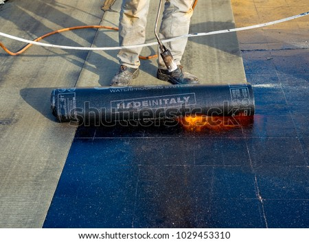 Worker preparing part of bitumen roofing felt roll for melting by gas heater torch flame. On the back of the sheath there is the stamp