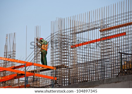 Worker preparing steel rods to concrete