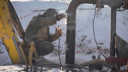 Worker produces pipe welding on the street. In winter, at low temperatures, it is difficult to mount the pipe wire.