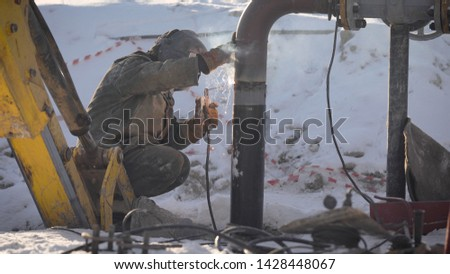 Worker produces pipe welding on the street. In winter, at low temperatures, it is difficult to mount the pipe wire. stock photo