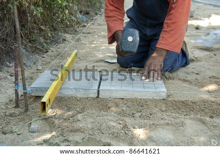 Worker puts sidewalk tiles. Walkway making