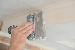 Worker putsty plasterboard ceiling in new building. Repairman works with plasterboard, plastering dry-stone wall, home improvement. A man makes repairs at home. Putty knife in male hand