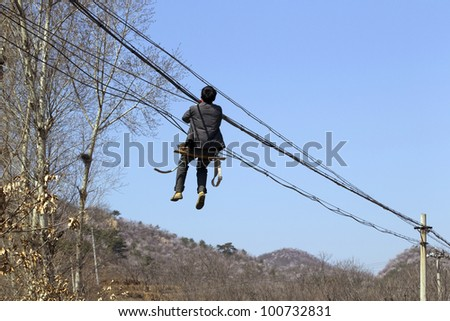 Worker repairing electrical power line, China - stock photo