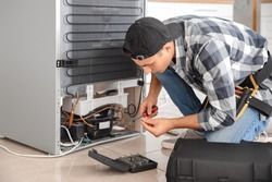Worker repairing refrigerator in kitchen