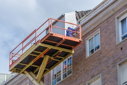 worker repairs the facade of a residential building on a basket of an industrial lift, bottom view