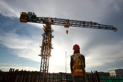 Worker, Rigger signal with crane at construction site