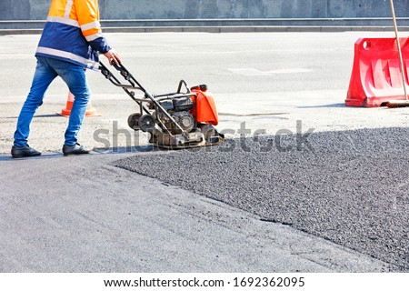 Worker road service use vibratory plate compactor compacting asphalt at road repair site. Foto stock ©