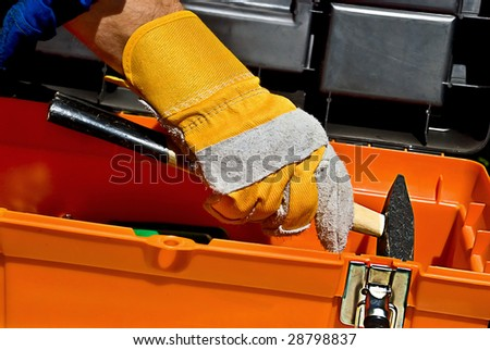 Worker's hand taking a hammer out of a toll box