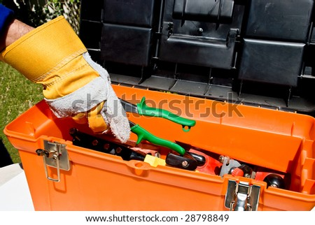 Worker's hand taking snips out of a toll box