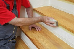 Worker sanding plank at stairs using sand paper