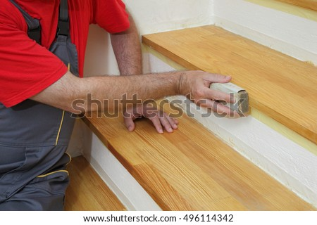 worker sanding plank at stairs...