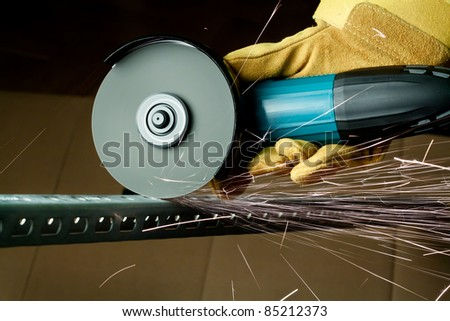 Worker sawing metal with electrical saw, grinder.