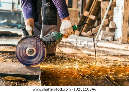 Worker sawing sheet metal with a chain saw. Work in production, sparks fly in different directions