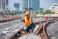 worker sitting on railway with hand touch helmet. young engineer sitting on railway inspection.