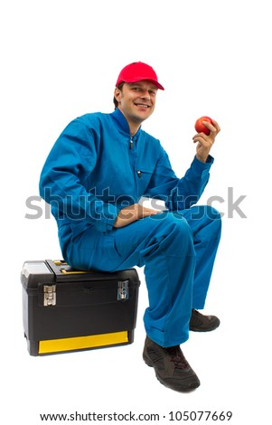 worker sitting on toolbox with red apple in hand