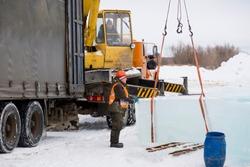 Worker slinger in orange reflective vest and helmet unloads ice panels