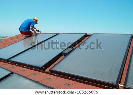 Worker solar water heating panels on the roof.