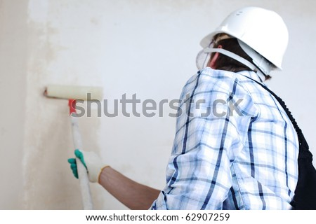 worker spends anchor roller on the wall