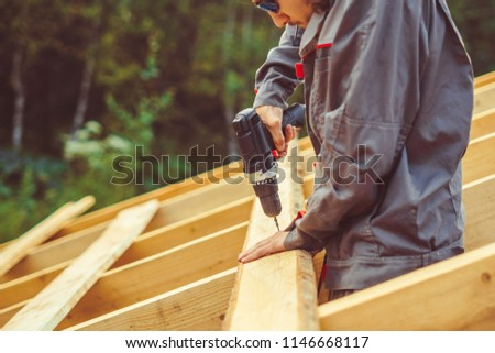 worker spins the screw into the Board on the roof
