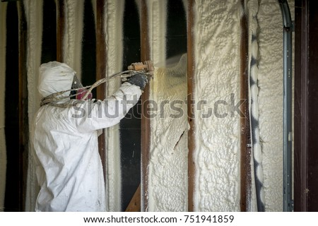 Worker spraying closed cell spray foam insulation on a home that was flooded by Hurricane Harvey  #751941859