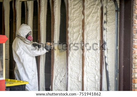 Worker spraying closed cell spray foam insulation on a home that was flooded by Hurricane Harvey  #751941862