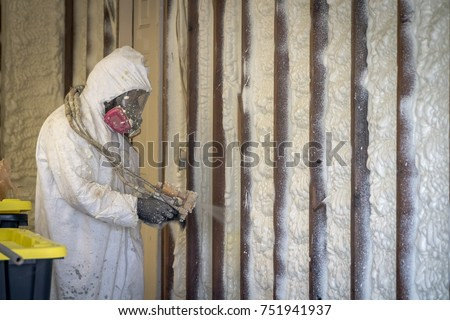 Worker spraying closed cell spray foam insulation on a home that was flooded by Hurricane Harvey  #751941937