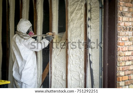 Worker spraying open cell spray foam on the wall of a home flooded by Hurricane Harvey #751292251