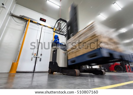 Shutterstock Worker Stand-on stacker truck used to lift and move the ready meals goods stock in cold room or freezer room.